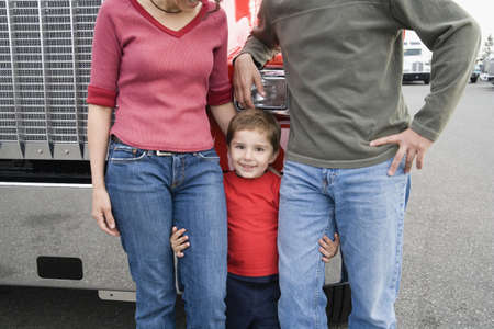 truck driver: Young boy standing with his parents
