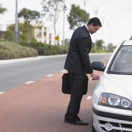 ostentatious: Businessman unlocking a car door LANG_EVOIMAGES