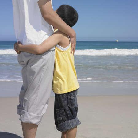 mujer mirando el horizonte: Padre abrazando a hijo en la playa