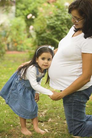 mujer ba�andose: Ni�a que escucha el vientre de su madre embarazada