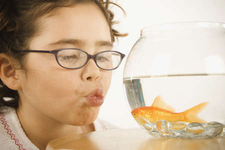 mischievious: Young girl making a kissy face for a goldfish
