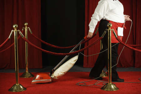 notoriety: Woman vacuuming the red carpet LANG_EVOIMAGES