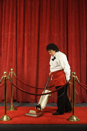 toiling: Woman vacuuming the red carpet LANG_EVOIMAGES