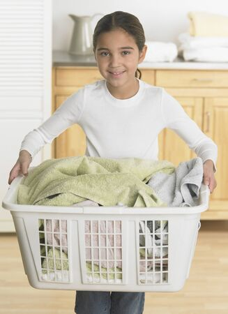 bambino: Young girl holding a laundry basket