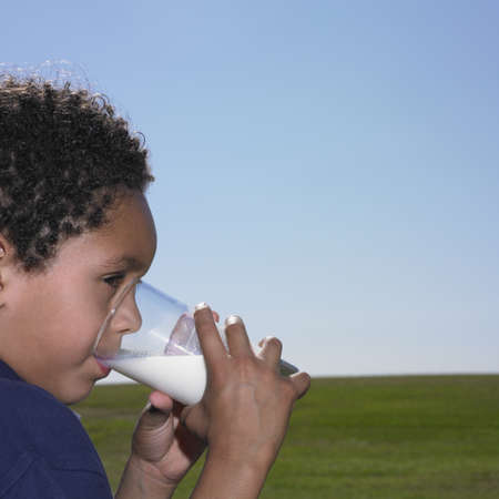 only 1 boy: Young boy drinking a glass of milk