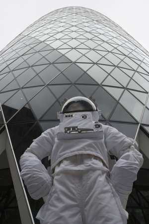 low  angle: Low angle view of an astronaut standing by a skyscraper LANG_EVOIMAGES