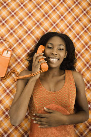 acknowledging: Young woman talking on the phone while lying on a checkered blanket LANG_EVOIMAGES