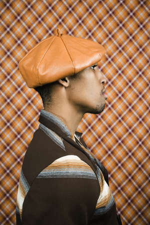 lower section view: Profile view of young man wearing a leather hat
