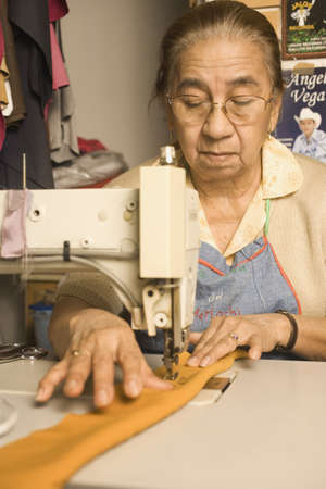 seller: Senior woman using a sewing machine LANG_EVOIMAGES
