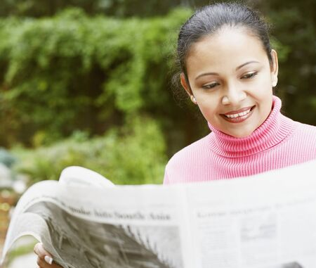 motioning: Young woman reading the newspaper