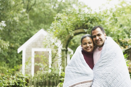 bedcover: Couple wrapped in a blanket outdoors LANG_EVOIMAGES
