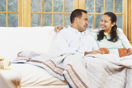 bedspread: Couple sitting on the couch under a blanket together
