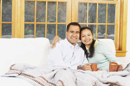 casualness: Couple sitting on the couch under a blanket together