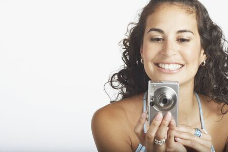 acknowledging: Young woman using a digital camera