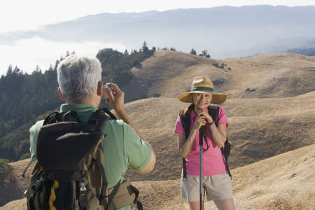 taking a wife: Senior man taking a picture of his wife on a hike