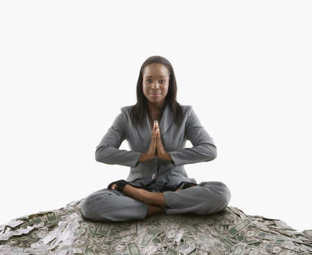 dollarbill: Businesswoman meditating on a mound of cash LANG_EVOIMAGES