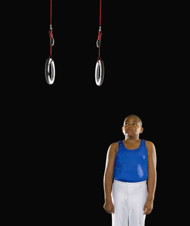above 30: Young boy unable to reach the gymnastic rings LANG_EVOIMAGES
