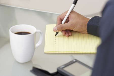 noting: Businesswoman writing on a yellow pad