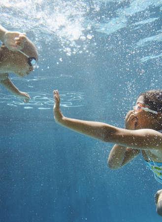 vacationing: Children waving to each other underwater