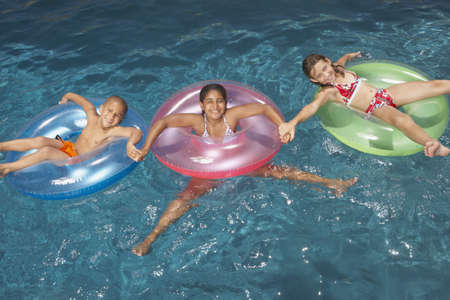 child swimsuit: Young girls floating in inner tubes LANG_EVOIMAGES