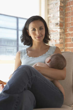 mid adult woman: Mother breastfeeding her baby