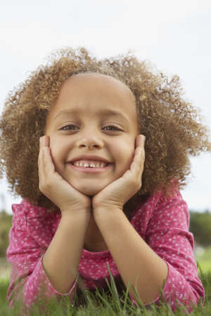 Young girl smiling for the camera in the grass Stock Photo