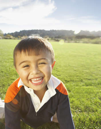 young boy smiling: Young boy smiling for the camera in the grass