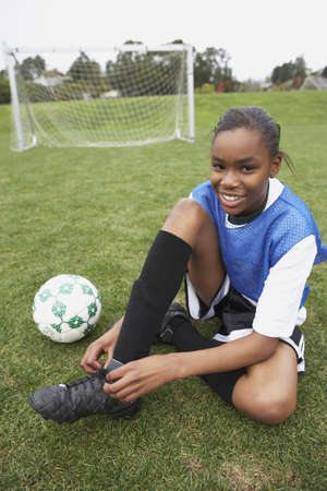 soccer cleats: Young girl tying her soccer cleats LANG_EVOIMAGES