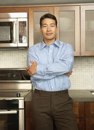 spectating: Young man posing for the camera in his kitchen