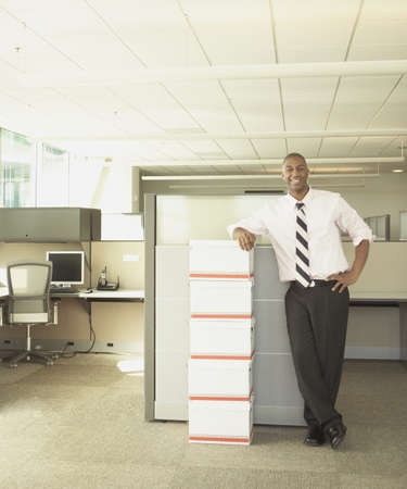 medium length: Businessman smiling for the camera in empty office space