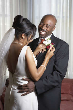 african american couple: Bride pinning flowers onto groomÃŒs lapel LANG_EVOIMAGES