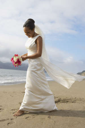 honeymooner: Bride walking barefoot on the beach LANG_EVOIMAGES