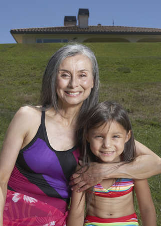 fond of children: Senior woman and her granddaughter posing for the camera