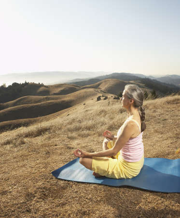 longshot: Senior woman meditating on a yoga mat outdoors