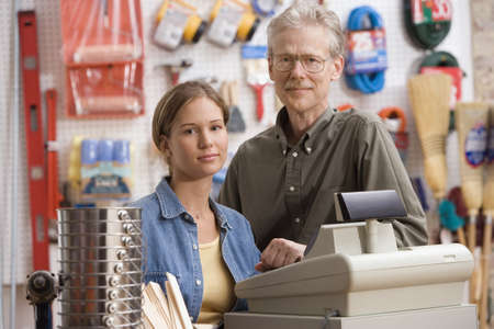 cash register: Father and daughter smiling for the camera in hardware store LANG_EVOIMAGES