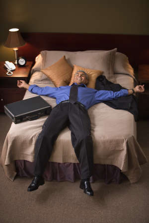 being the case: Businessman relaxing on hotel bed LANG_EVOIMAGES