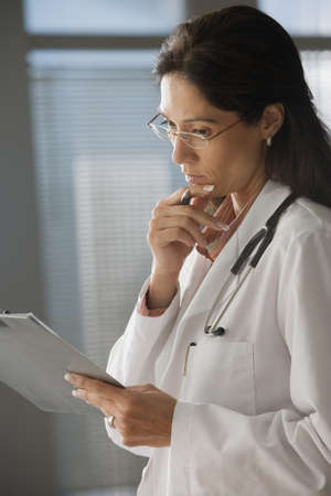 toiling: Female doctor examining clipboard