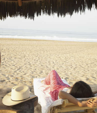 casualness: Young woman relaxing on the beach LANG_EVOIMAGES