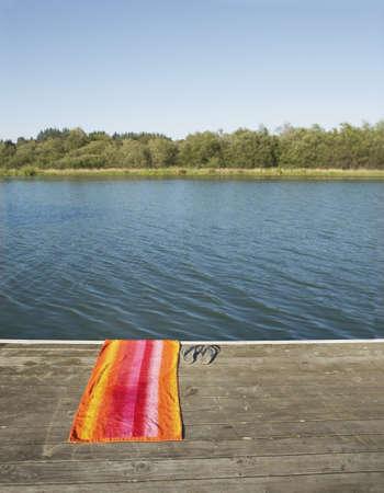 flipflops: Towel and flip-flops by lake
