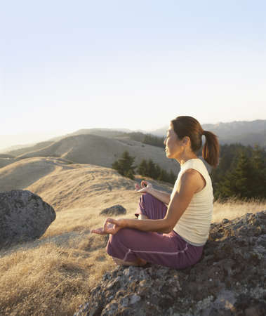 introspective: Middle-aged woman meditating outdoors