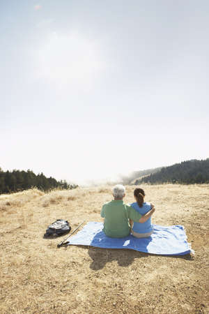 clear path: Senior couple sitting on a blanket outdoors
