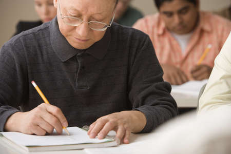 solicitous: Mature man writing during class