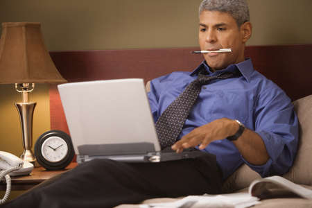 triumphing: Businessman using a laptop in his hotel room