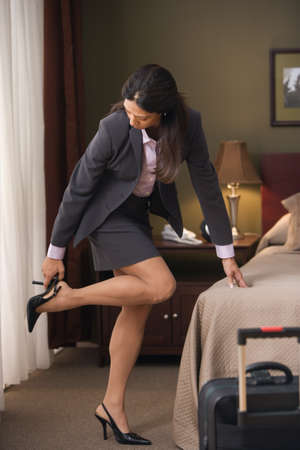 Businesswoman putting on her heels in hotel room LANG_EVOIMAGES