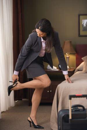 Geschäftsfrau, die auf den Fersen in Hotelzimmer LANG_EVOIMAGES
