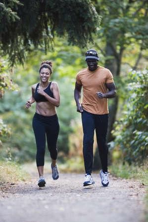 gratifying: Couple jogging on gravel path