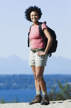 african american woman smiling: Young woman hiking LANG_EVOIMAGES