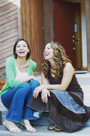 gratifying: Young women laughing together LANG_EVOIMAGES