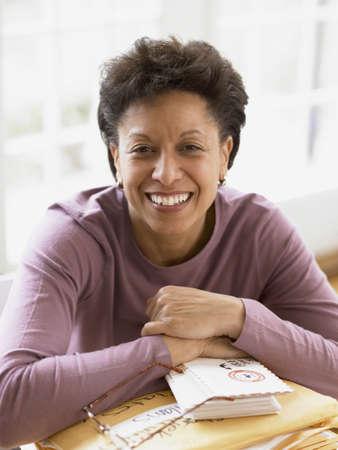 mujeres sentadas: Mujer de mediana edad sonriendo para la cámara en su escritorio