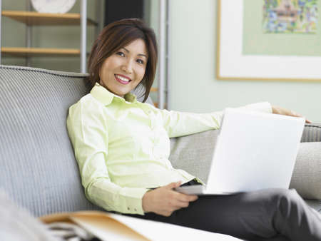 low spirited: Businesswoman using a laptop on a couch